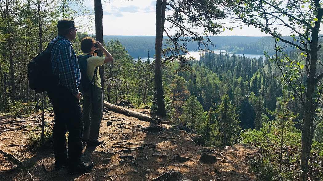 Kaksi retkeilijää seisoo kalliojyrkänteen päällä tasanteella. Toinen kiikaroi kanjoniin. Taustalla vesistö.