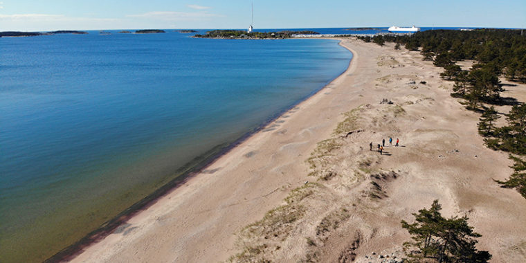 Pitkä hiekkaranta ja meri kuvattu ilmasta, ihmisiä kulkee hiekalla, missä on matalaa kasvillisuutta.
