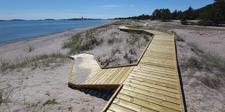 Poikittaisista laudoista tehty kulkutie, lankkupolku, hiekkarannalla Hangon Tulliniemenrannassa.