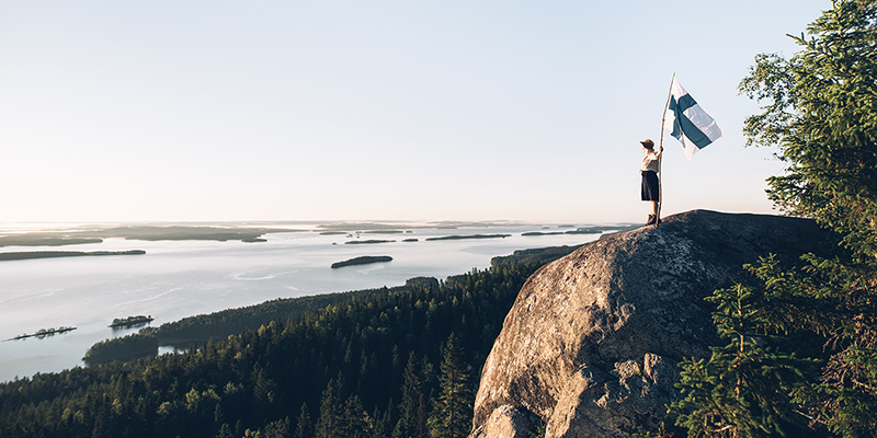 Ihminen seisoo korkealla kalliolla Kolin huipulla ja katsoo järvimaisemaa, kädessä tanko, jossa Suomen lippu.