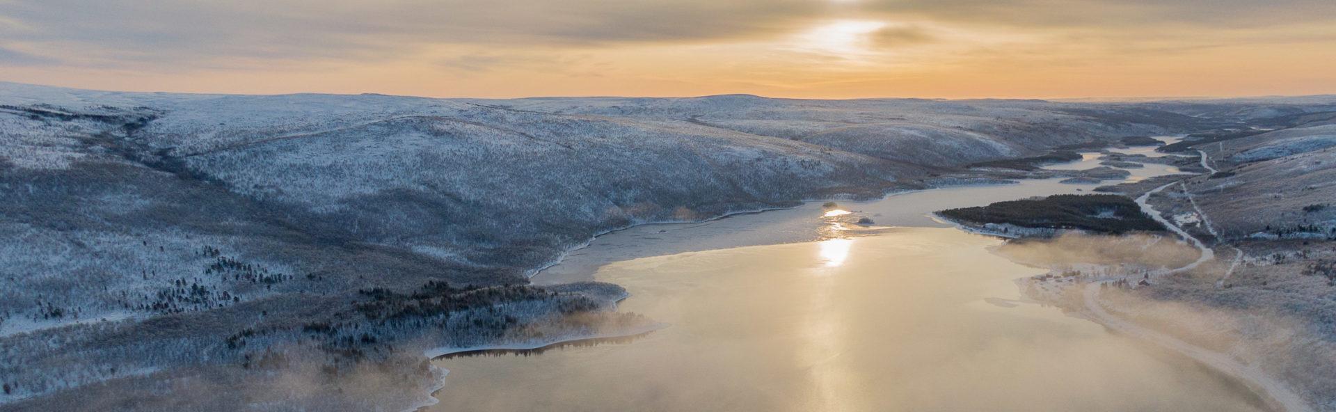 Ilmasta kuvattu talvinen maisema Utsjoelta, kuvassa näkyy vesistö ja tuntureita.