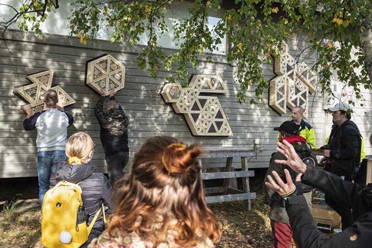 Hyönteishotelleja kiinnitetään Limingan luontokeskuksen ulkoseinään.