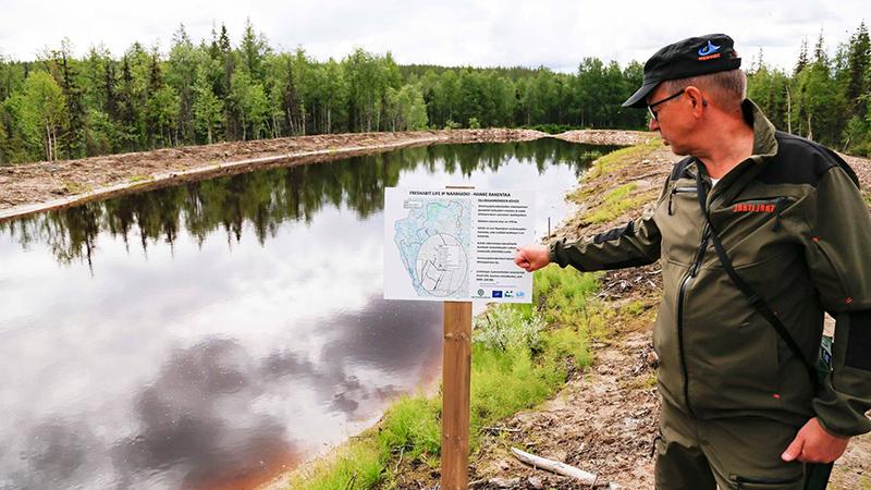 Mies osoittaa infotaulua vesialtaan rannalla, ympärillä metsää.