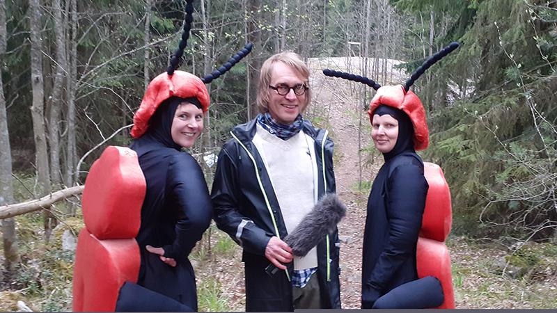 Kuvassa on kolme ihmistä, joista kaksi on pukeutunut hyönteiseksi nimeltään punahärö. Heidän keskellään on toimittaja mikrofoni kädessään.