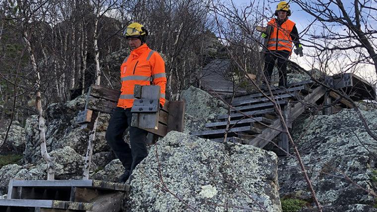 Kaksi ihmistä turvakypärä päässä laskeutuu alas puisia portaita kivikkoisella mäellä ja kantaa irrotettuja porraslautoja mukanaan.