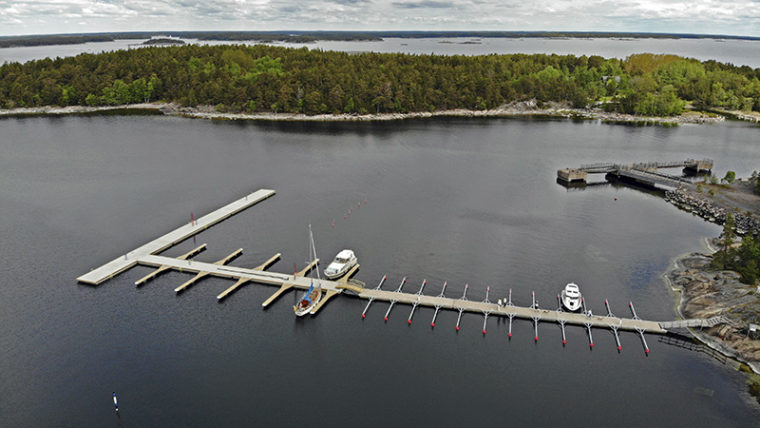 Aerial view of a long jetty. Several woody islands further away.
