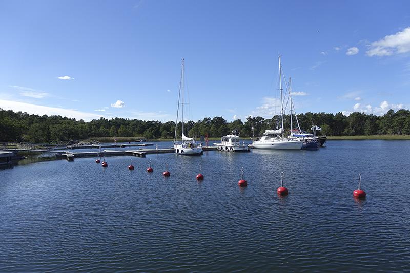 Lång brygga med flera förtöjda båtar. Längre bort från bryggan finns bojar.