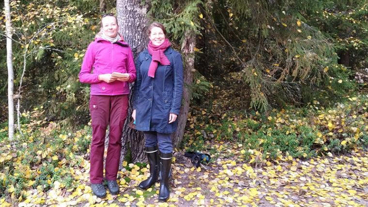 Kaksi henkilöä seisoo vierekkäin puunrungon edessä syksyisessä metsässä.
