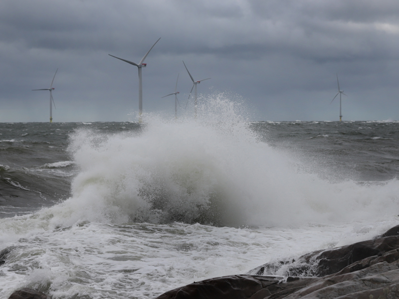 A big wave hits the cliff. At sea, behind the wave, five wind turbines can be seen.