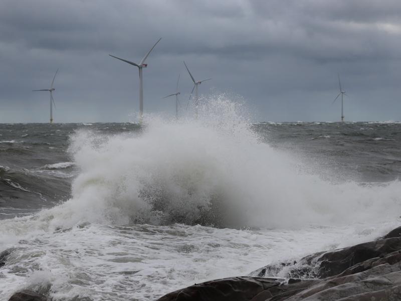 En stor våg träffar klippan. Till sjöss, bakom vågen, kan man se fem vindkraftverk.