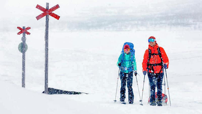 Kaksi nauravaa ihmistä hiihtää lumisateessa, toisella reppu selässä, toinen vetää ahkiota. Vieressa reittiviittoja, takana lumisia tuntureita.