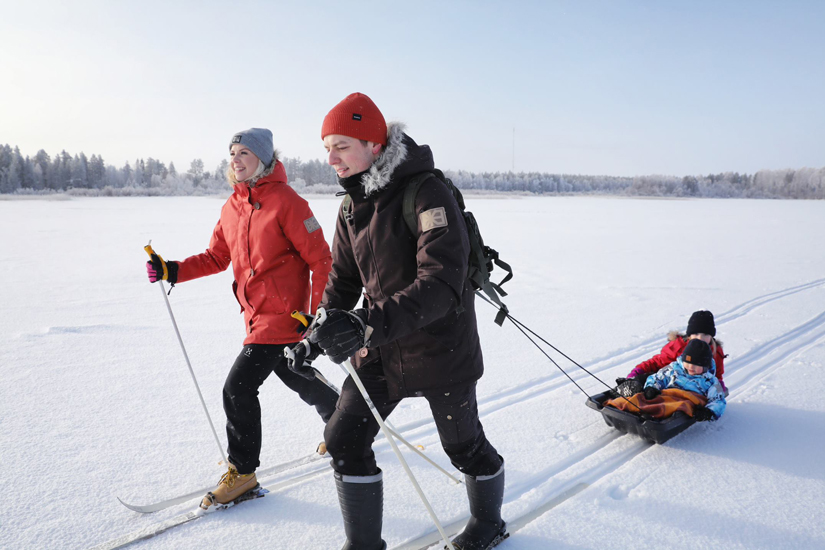 Mies ja nainen hiitävät järven jäällä. Mies vetää perässään pulkkaa, jossa on kaksi lasta.