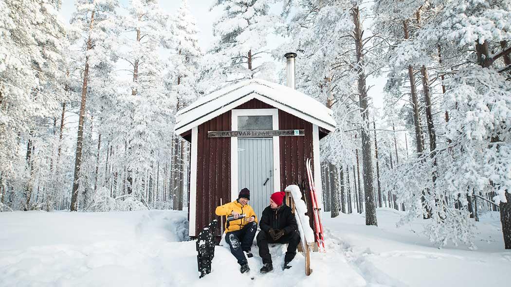 Kaksi retkeilijää istuu kahvitauolla pienen rakennuksen lumisilla portailla. Taustalla on luminen metsä.