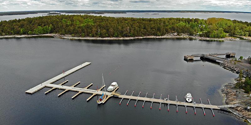 Pitkä laituri,jossa 30 venepaikkaa. taustalla runsasta puustoa kasvava saari ja merta