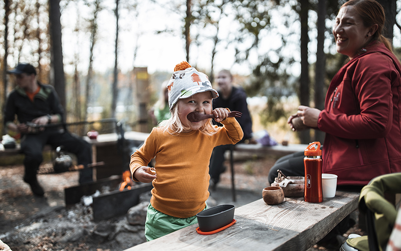 A smiling child eating with a wooden spoon outdoors. Other people and a fireplace in the background.