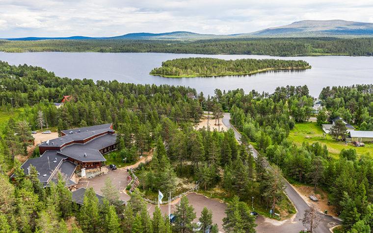 Etualalla puiden keskellä rakennus ja teitä ilmasta kuvattuna, taustalla järvi ja tuntureita.