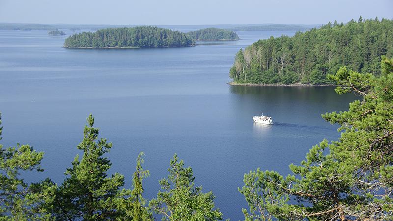Puunlatvojen tasalta avautuva kesäinen järvimaisema, missä saaria ja laiva.