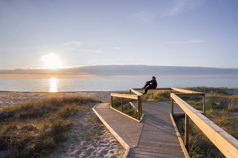Henkilö katsoo auringonlaskua hiekkarannalla esteettömällä polulla.