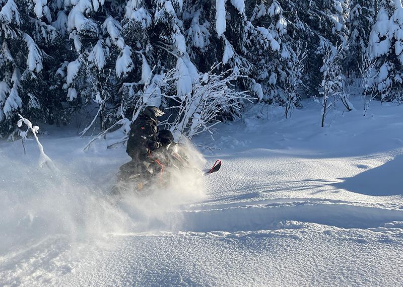 Moottorikelkka ajaa umpihangessa aurinkoisessa talvisäässä.