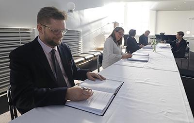 Ihmisiä istuu pöydän ääressä kirjoittamassa asiakirjoihin.