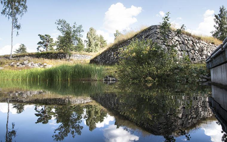 Kivestä ladottuja matalia muureja veden äärellä.