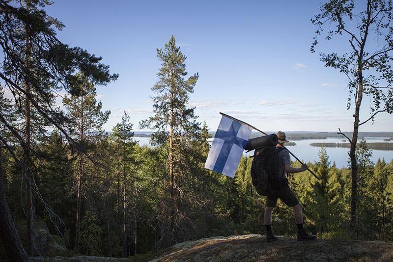 Retkeilijä seisoo vaaran laella katsomassa järvimaisemaa. Retkeilijällä on kädessään kookas Suomen lippu ja selässään rinkka.