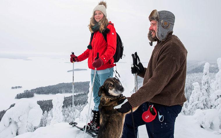 Kaksi ihmistä ja koira korkean vaaran huipulla talvella, maasto paksun lumen peitossa.