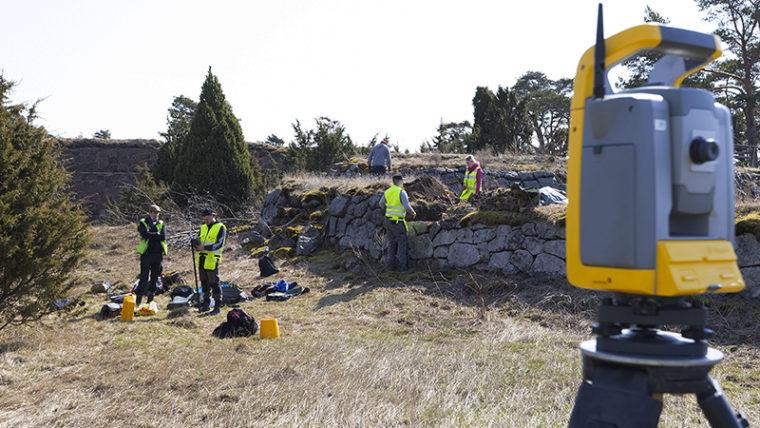 Arbetare vid gammal stenmur på Svartholms fästningsö. I förgrunden en mätningsapparat.