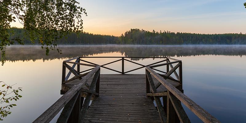 Kaiteilla varustettu puulaituri tyynen järven rannalla kesäauringon laskiessa.