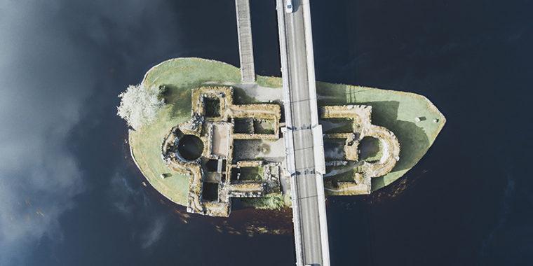 Linnanrauniot pienellä saarella, raunioiden yli menee ajotie. Kuvattu ylhäältä päin.