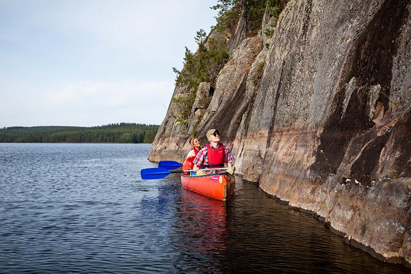 Kaksi melojaa kanootissa jyrkän kallioseinämän vieressä.
