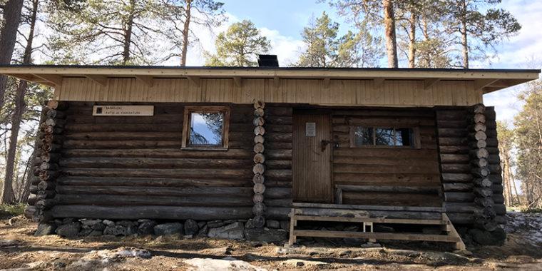 Maalamaton, pieni hirsirakennus, jossa laudasta uusi katto.