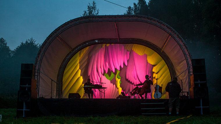 Kaarevakattoinen esiintymislava ulkona, lavalla yksi muusikko kosketinsoittimen ääressä, toinen soittaa selloa.