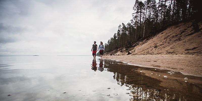 Mies ja nainen kävelevät rantavedessä. Järven törmällä kasvaa mäntynetsä.