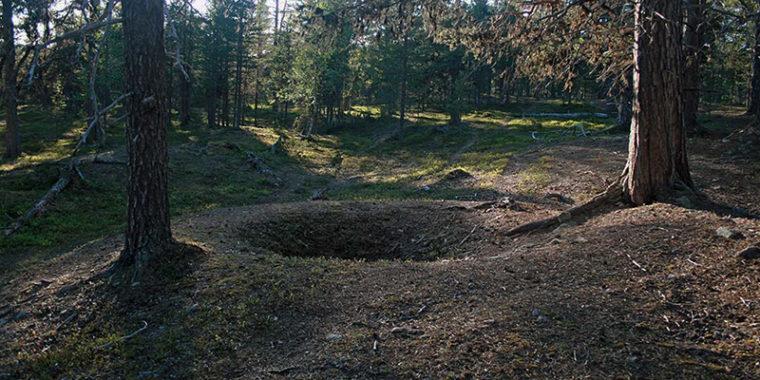 Mäntyjen ja kuusien keskellä metsässä pyöreä maakuoppa.
