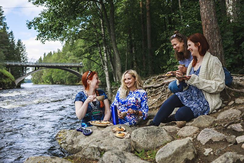 Neljä naista istuu virtaavan joen rantakivillä juomassa kahvia ja syömässä mustikkapiirakkaa. Kaikilla naisilla on sinivalkoiset vaatteet ja he nauravat.