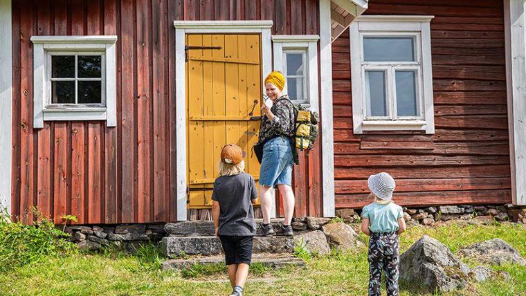 Nainen ja kaksi lasta vanhan puurakennuksen portailla, naisella avain oveen.