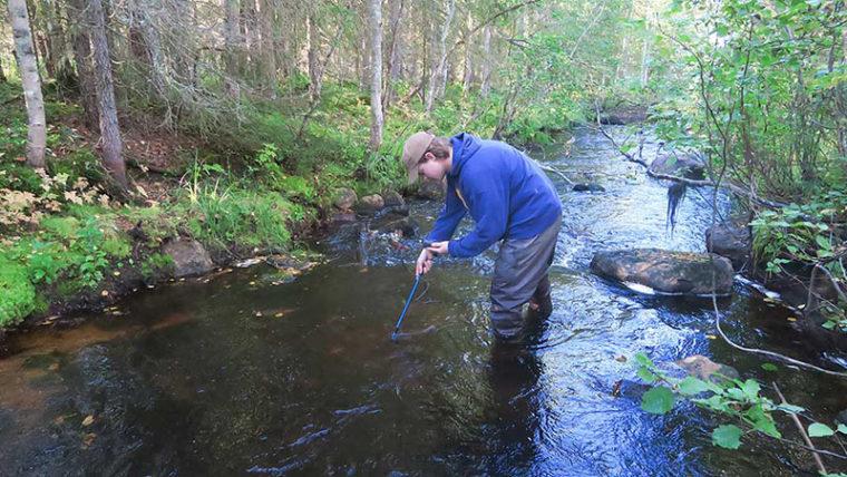 Mies seisoo joessa ja tutkii joen pohjaa laitteella.