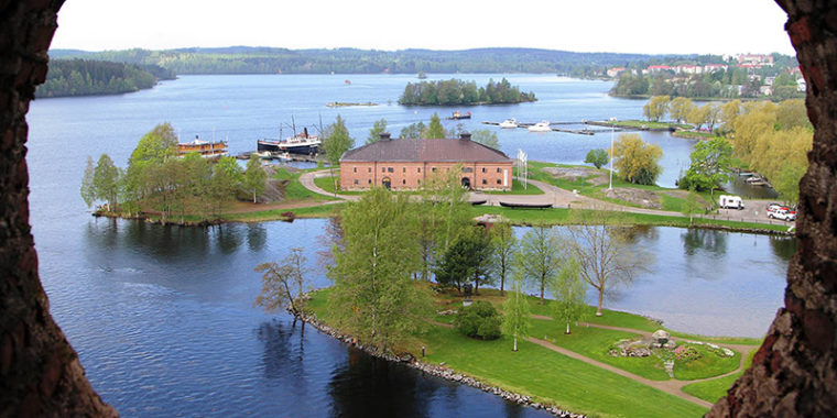 Valokuva otettu ylhäältä, kivilinnan tornin aukosta. Alhaalla järvi ja niemellä suuri, vanha tiilirakennus ja sen takana vanhoja laivoja laiturissa.