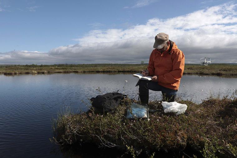 Tutkija on polvistuneena veden äärellä ja kirjoittaa muistiinpanoja vihkoon.