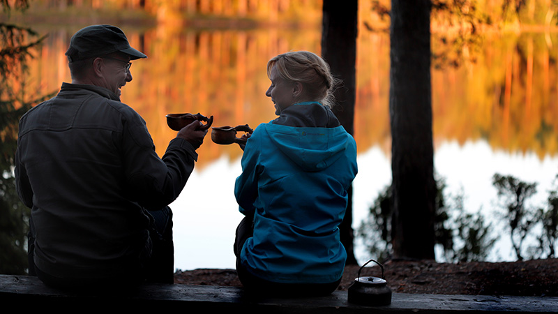 Mies ja nainen istuvat penkillä ja juovat kuksasta kahvia järven rannalla.