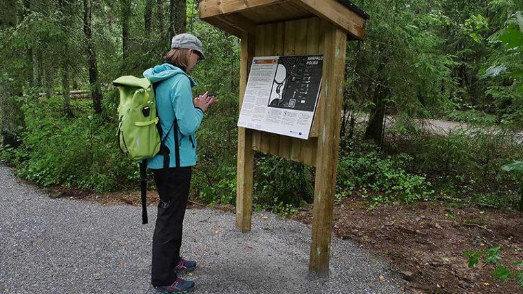 Ihminen reppu selässä sorapolulla metsässä infotaulun edessä.