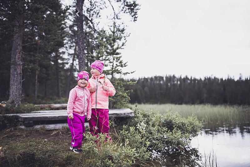 Kaksi lasta seisoo lammen rannalla. Toisella lapsella on kädessä valkoinen höyhen.