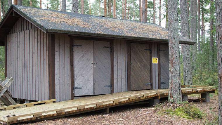 Puinen, harjakattoinen rakennus, jossa leveät ovet ja vieressä puinen, leveä ramppi rakennuksen seinän suuntaisesti.