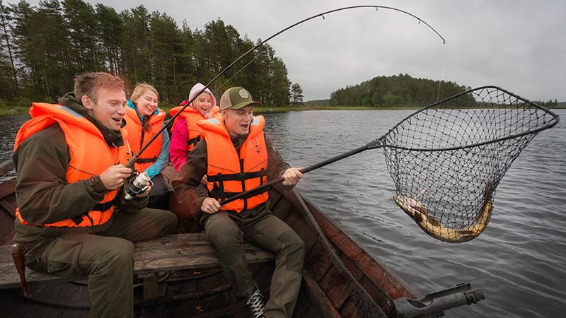 Nuoria miehiä ja naisia istuu veneessä kalastamassa. Miehet ovat nostaneet kalan haaviin.