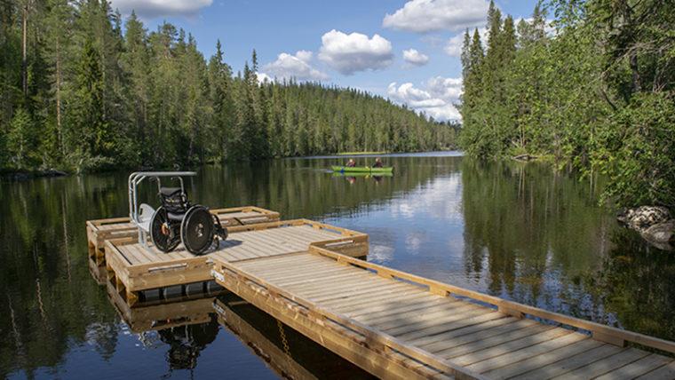 Järven rannalla puinen laituri, laiturilla pyörätuoli ja teline, jonka avulla voi laskeutua pyörätuolista kanoottiin ja nousta pois.