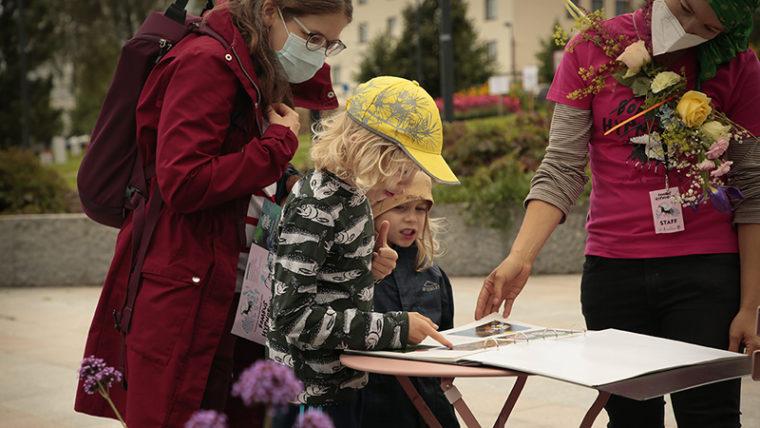 Kaksi lasta ja aikuinen selaavat kuvakansiota, jota esittelevällä ihmisellä kukkakimppu kiinnitettynä rintaan.