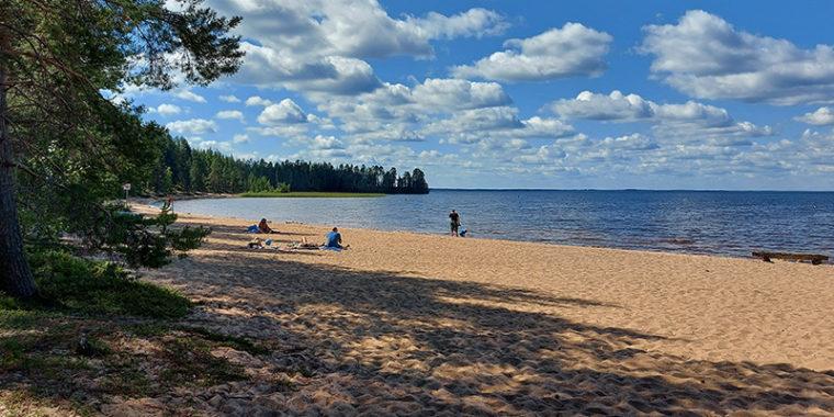 Suuren järven hiekkarannalla muutamia ihmisiä kesäpäivänä, rannoilla havumetsää.